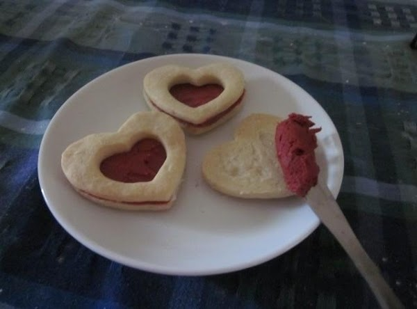 Spread filling between two cooled shortbread cookies (Top cookie has the cut-out heart in...