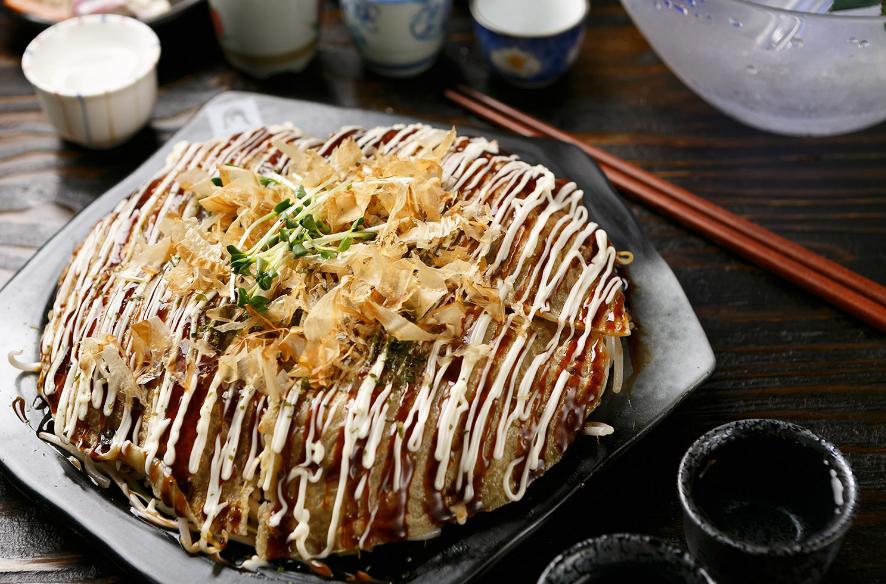 Okonomiyaki, comida japonesa que consiste en una masa con varios ingredientes cocinados a la plancha.