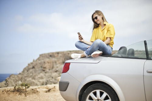 Woman in Yellow Blouse and Blue Jeans Taking Selfie While Sitting on Car