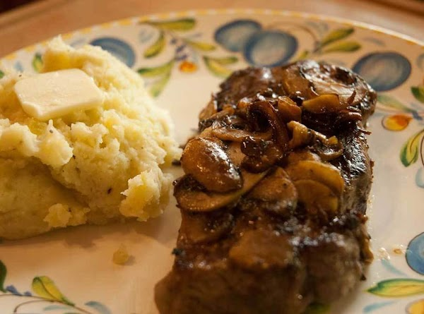Steak on a plate with mushrooms and mashed potatoes.