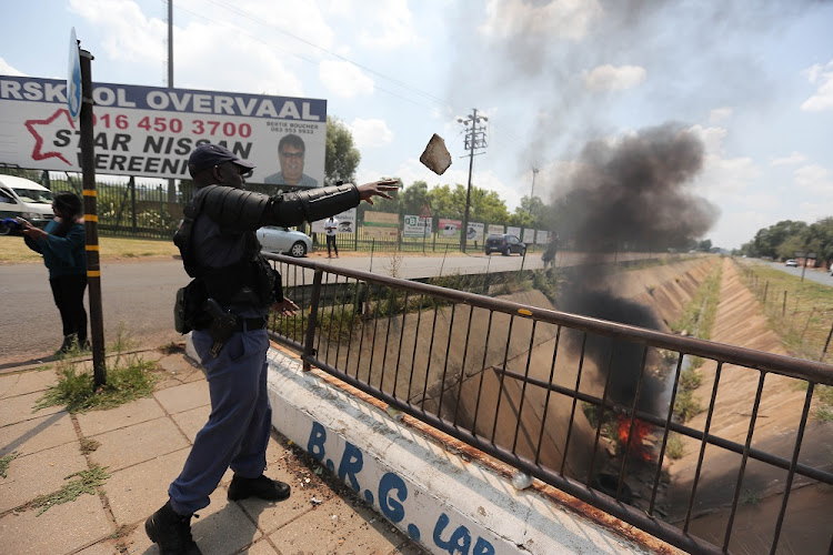 FILE PHOTO: Members of the police clear police barricades outside Hoerskool Overvaal in Vereeniging on the second day of protests at the school.
