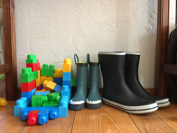 Stack of blocks next to two pairs of rain boots