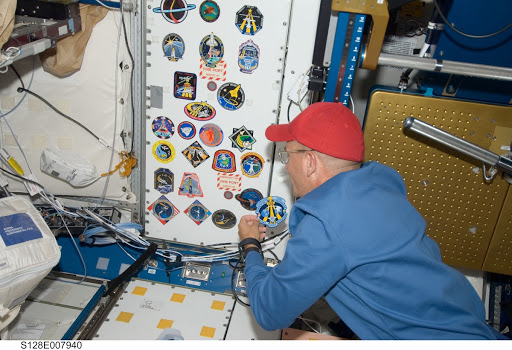 Sturckow adds STS-128 crew patch to wall in Node 1 Unity