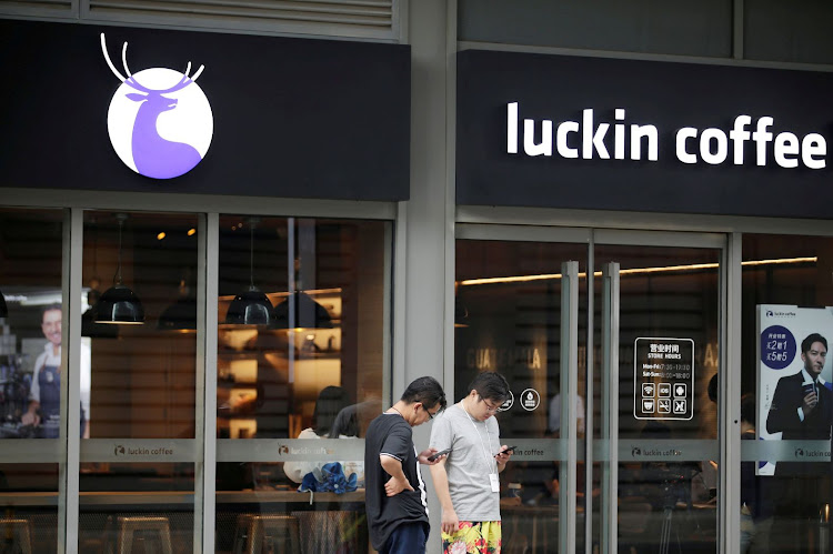 Men check their mobile phones outside a Luckin Coffee store in Beijing, China, in this file photo taken on July 17 2018. Picture: REUTERS/JASON LEE