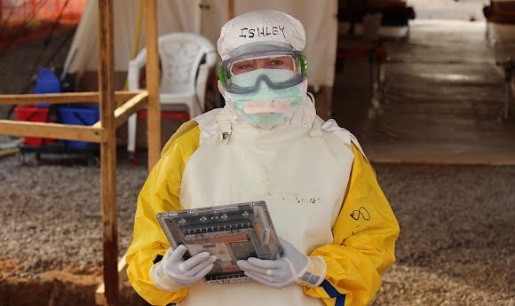 An MSF field worker in protective gear looks into the camera while using a tablet to access Project Buendia.