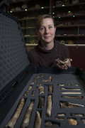 A hand out image made available by the University of the Witwatersrand, shows 'Rising Star' hominid fossil excavation expedition collaborator Marina Elliott pictured with parts of the skeleton of the homo Naledi in the Wits bone vault at the Evolutionary Studies Institute at the University of the Witwatersrand. AFP