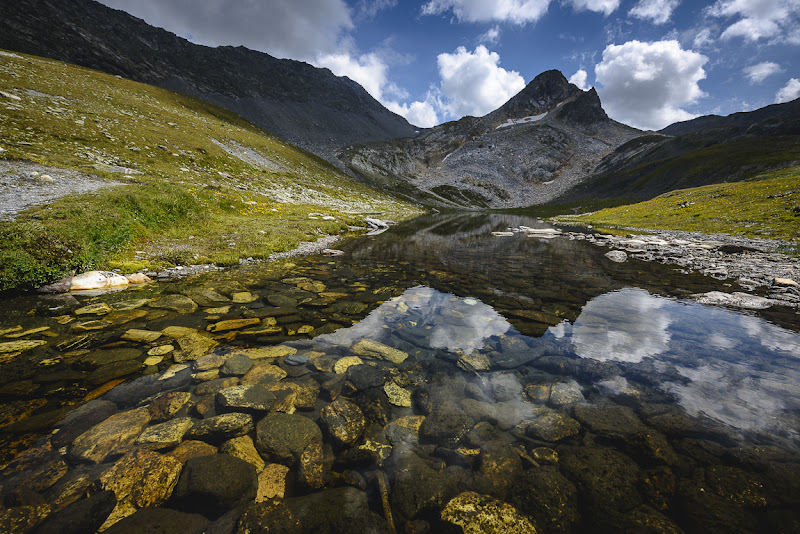Photo: Crystal clear (view large) From my blog: http://www.niophoto.com/crystal-clear/  A few weeks ago, I was hiking up at the Lacs de Fenêtre near the Grand Saint-Bernard pass at the Swiss/Italian border. This area is well known for its nice lakes as well as its view on the majestic Mont Blanc massif. After shooting the larger lakes, I ran into this small mountain lake. The bottom of the lake is covered with copper colored rocks, which is typical for that region. In the background you see a Mountain called Point de Drône … which I climbed afterwards.  I captured this image using my 14-24 f/2.8 wide angle lens. Shot it at 14mm to emphasize the rocky bottom of the lake and to give the image a bit of extra depth. I used a 2-stop Singh-Ray graduated filter to control the brightness of the sky a bit. The image was processed in Adobe Lightroom 4.1. Hope you like it!  Dedicating this one to my real life friend +Athena Carey, because she loves mountain lakes so much :D  #BreakfastClub +Breakfast Clubby +Gemma Costa, #PlusPhotoExtract by +Jarek Klimek,  #LandscapePhotography +Landscape Photographyby +Margaret Tompkins,  #ThirstyThursdayPics by +Mark Esguerra,  #mouıntainphotos +Mountain Photosby +Baki Karacay, #10000photographersaroundtheworld +10000 PHOTOGRAPHERS around the Worldby +Robert SKREINERand #NatureArtThursday by +Dane Clinganand +Trisha Standard #D800E  #spcfeature +Low Angle Photography