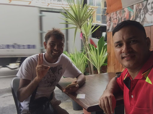 Dnyan and new friend, Gyan, pose for a selfie together at a restaurant.