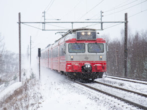 Photo: Local train on the main line out of Drammen towards Oslo, in a cold and snowy day, leaving a cloud of drifting snow behind