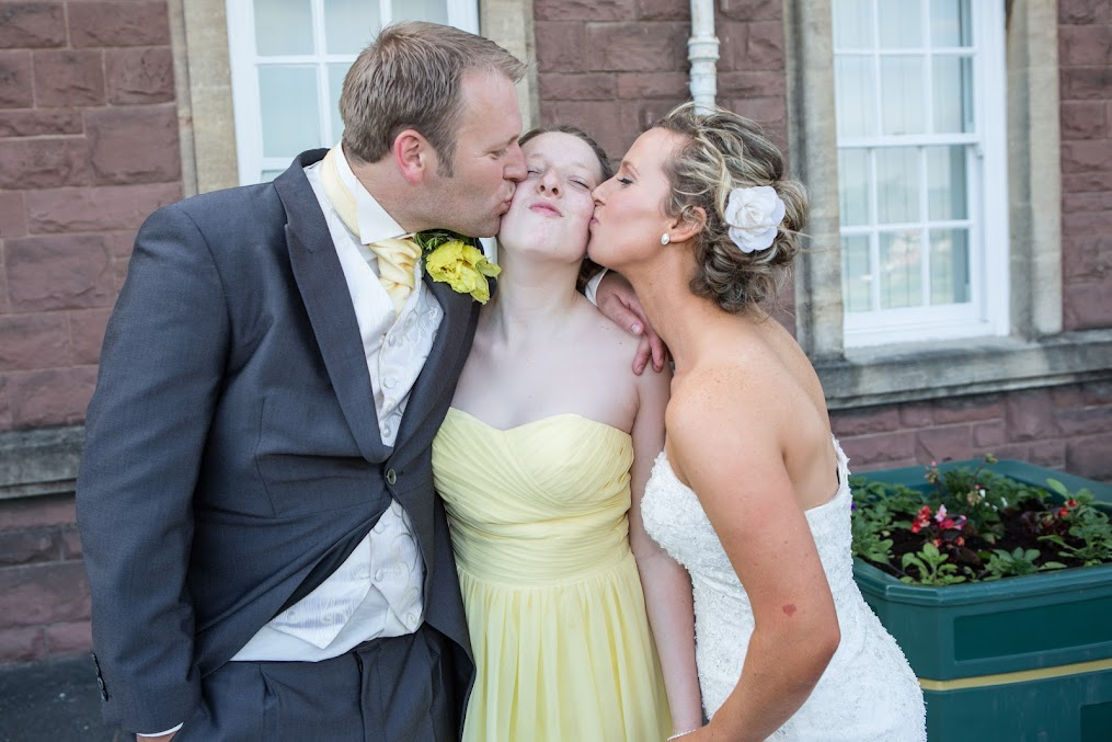wedding-couple-kissing-their-doughter
