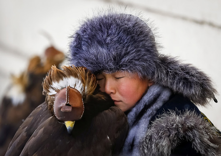 A young hunter rests next to his tamed golden eagle during an annual hunters' competition at Almaty hippodrome in Kazakhstan.