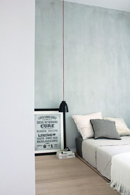 A leaning canvas and a stack of books beside bed