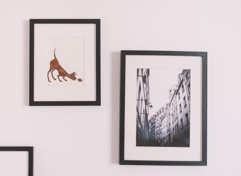 Two framed pictures, one a drawing of a dog and the other a photograph of a city street