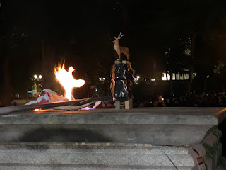 A tiny elk placed atop a bundle of sticks taped together. There is a small fire nearby as a flag burns on what was the statues base. Photo by: @45thabsurdist