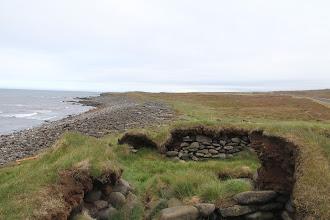 Photo: een ruine, veel drijfhout op het strand