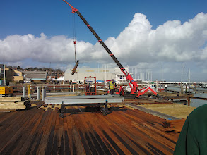 Photo: The top section of one of the old piles is lifted away on 26th February. The new cap will be fitted at low tide, and then the next steel joist lowered into position on the following high tide.