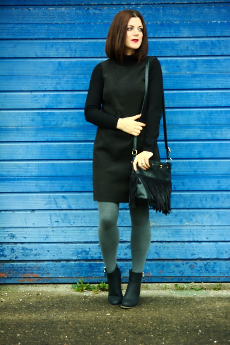 Grey leggings worn under black pinafore