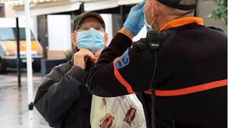 Un hombre recibe indicaciones sobre cómo colocarse la mascarilla, en la estación intermodal de Palma.