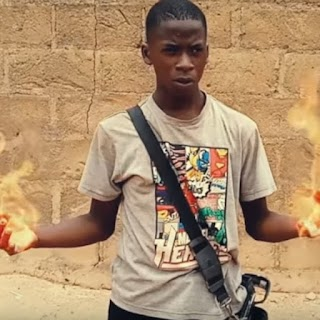 A young boy stands in front of the camera with fire in his hands, an effect created with technology.