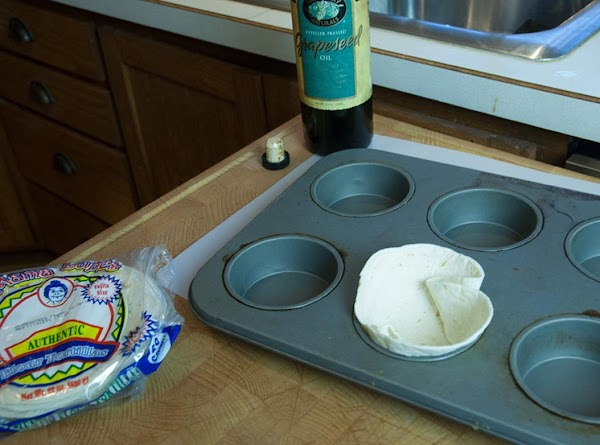 Carefully press the tortilla into the cup of the muffin tin or the ramekin.