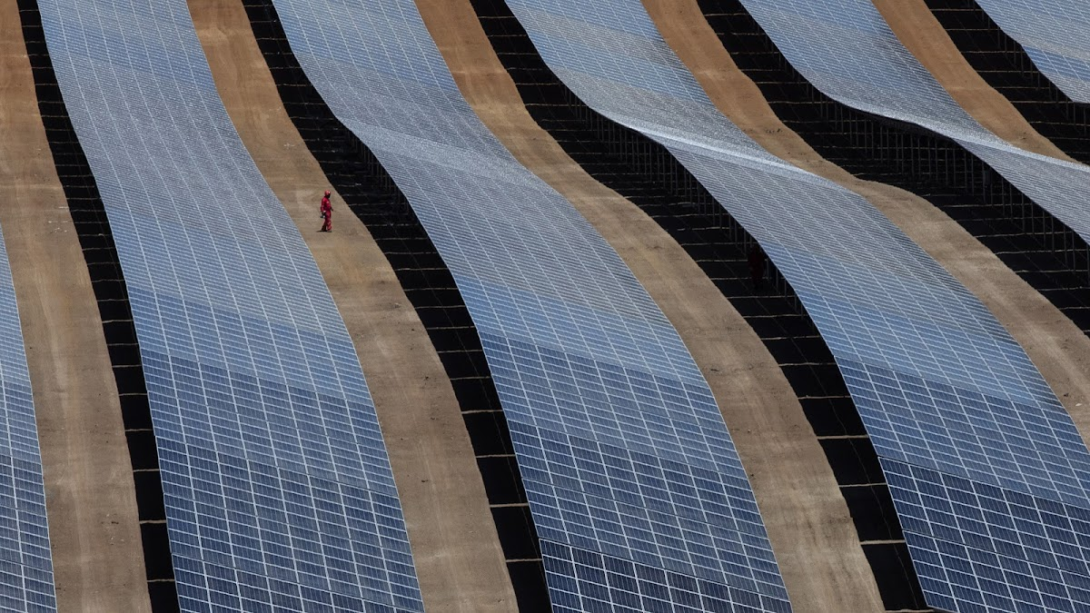 Wide angle drone photo of a solar technician surrounded between rows of solar panels