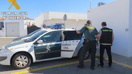Dos Guardias Civiles meten a un detenido en el coche patrulla.