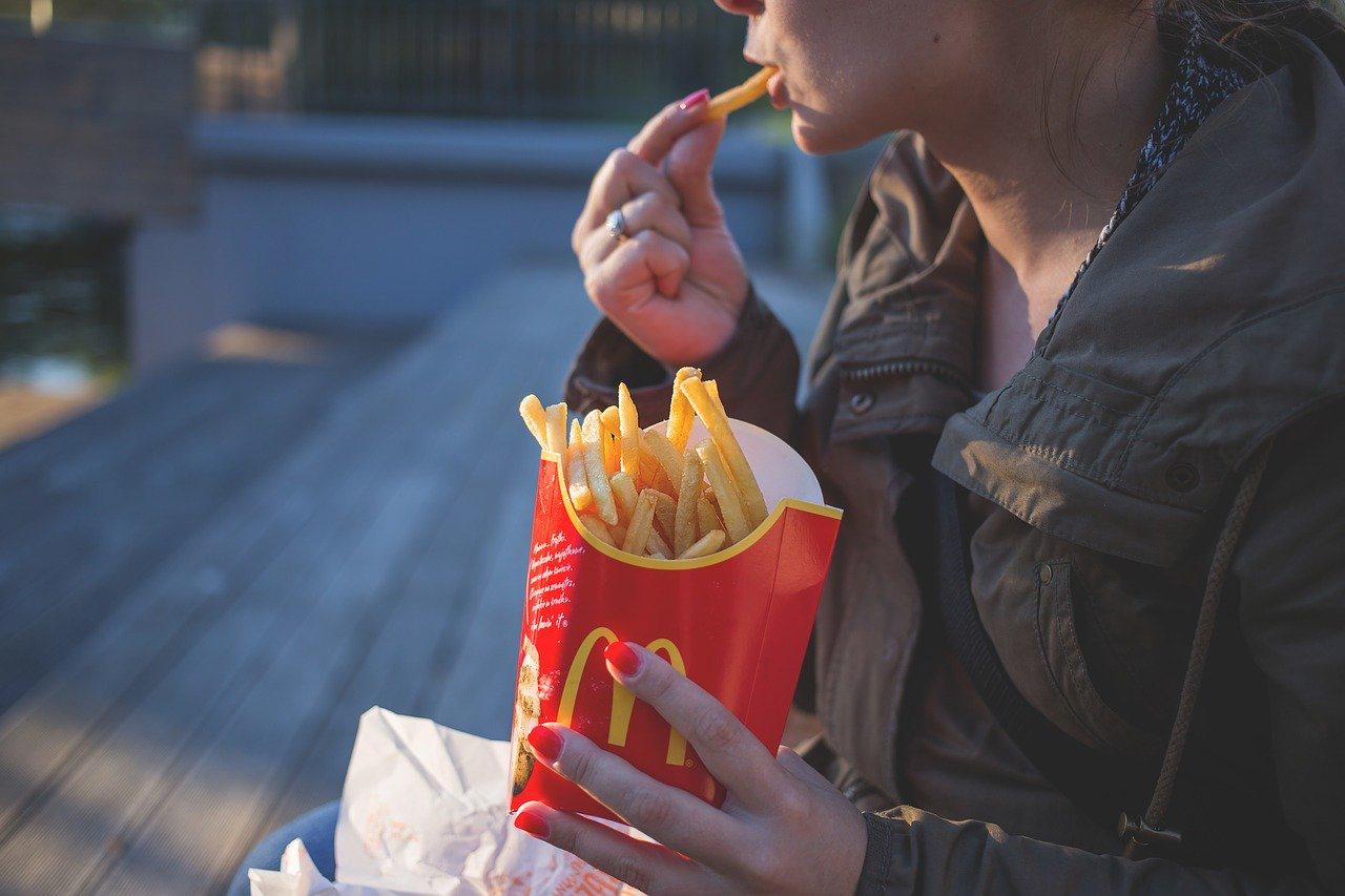 women eating fast food fries