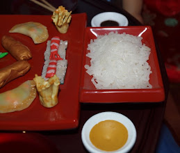 "Photo: The rice is made with the clay extruder.  We used ""translucent"" clay (without any added color) to get the cooked rice look.  The egg rolls were made with gold clay and wrapped around little rolls of aluminum foil.  The pot stickers were made by mixing translucent clay with a little bit of beige, which is why you can see the filling, which is little bits of brightly colored clay.  After it was baked, we painted the edges brown.  Everything is coated with clear gloss varnish, to make it look greasy and yummy."