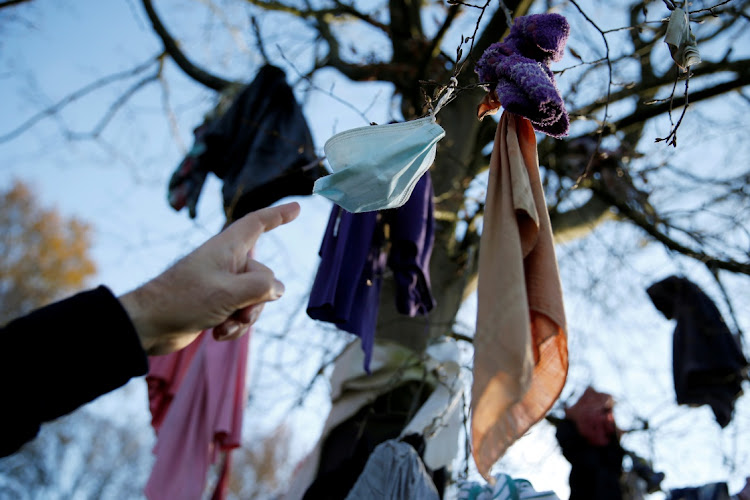 A protective mask hangs from 'L'arbre à loques', a 'healing' tree to which people attach cloths as a ritual for good health according to Celtic tradition, amid the Covid-19 pandemic in Hasnon, France. Picture: REUTERS/Pascal Rossignoll