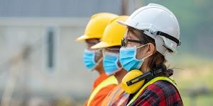 Mit geringem Abstand: Drei Arbeiterinnen mit Schutzhelm und Coronamaske.