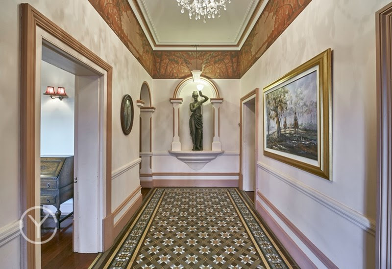 Tessellated tiles line the foyer's floor and a bronze statue sets the scene of a bygone era.
