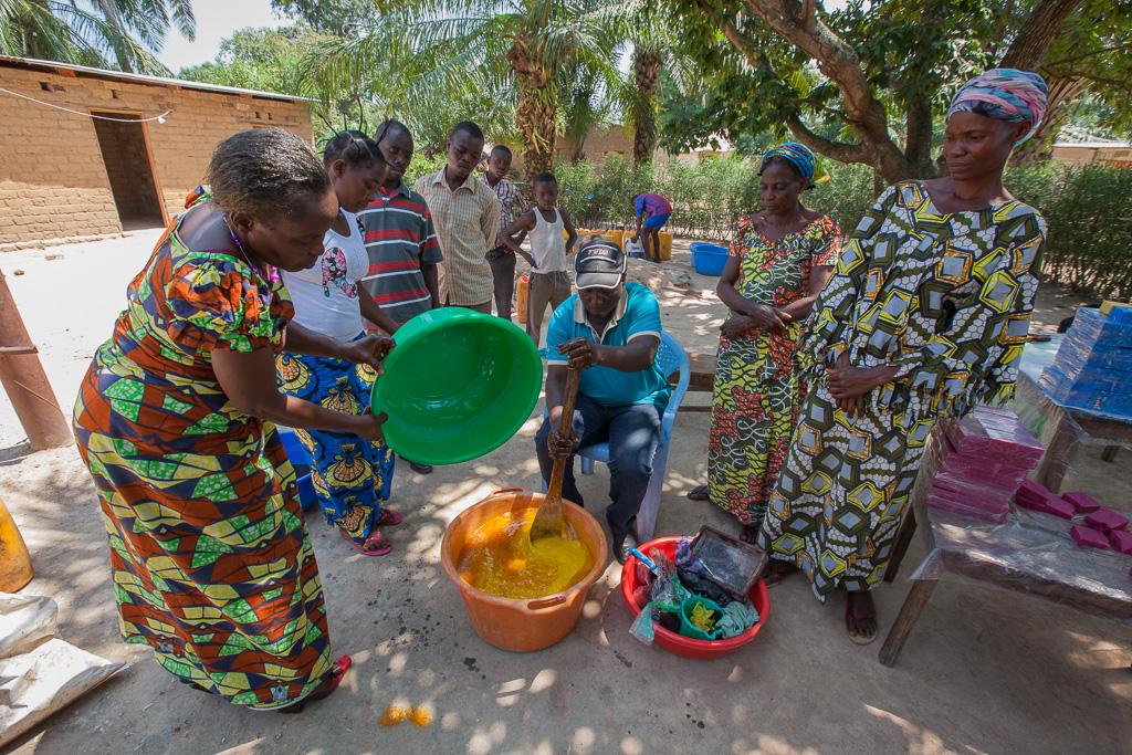 工芸品の石けん作りを学ぶ、明るい色のドレスを着たマノノ村の人々。将来は産業としての石けんビジネスを立ち上げたいと考えています。