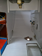 Photo: under sink & galley dry storage area painted save for hole awaiting new sink drain through hull fitting.