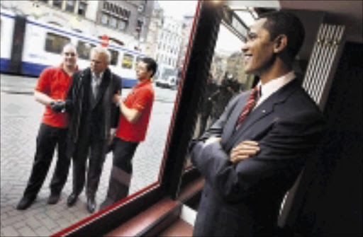 UNREAL: A wax figure of Barack Obama is on display at Madame Tussauds Wax Museum, as workers carry a wax figure of George W Bush outside the building in Amsterdam, the Netherlands. Obama's figure was also unveiled at Madame Tussauds in London, Berlin, New York and Las Vegas.  19/01/2009.Evert Elzinga. © AP.