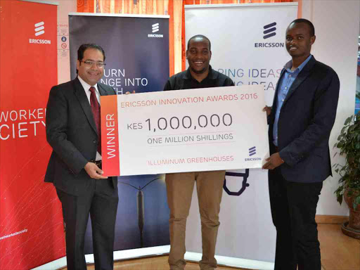 Ericsson Kenya managing director Aakaash Seghal hands a $10,000 dummy cheque to lluminum Greenhouses co-founders Taita Ngetich and Brian Bett, who won the Ericsson Innovation Award for sub-Saharan Africa. /COURTESY