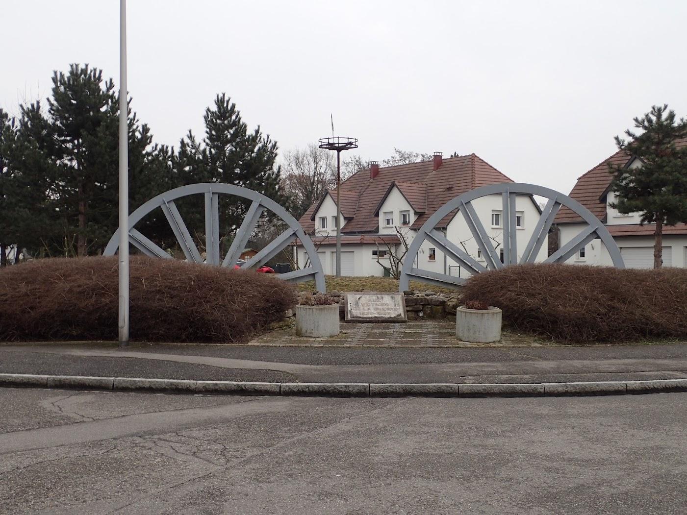 Monument aux morts Staffelfelden avec des roues de chevalement de puits de mine