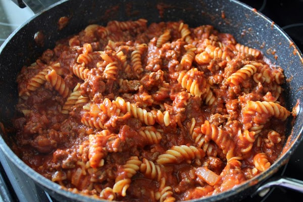 Tomato sauce and spices combined with pasta in a pan.