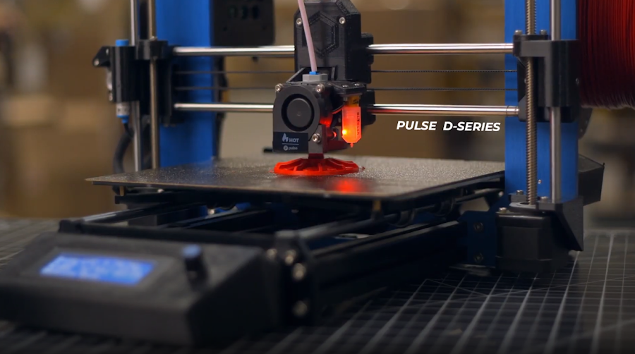 An older D-Series Pulse 3D printing a small housing in red PRO Series Tough PLA.