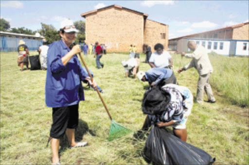 LEADING BY EXAMPLE: Gauteng education MEC Barbara Creecy leads the clean-up team at Bokamoso Secondary School in Thembisa yesterday ahead of the start of the school term on Wednesday. Pic. MUNYADZIWA NEMUTUDI. 10/01/2010. © Sowetan.