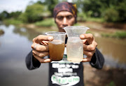 Environmental activist Deni Riswandani holds up cups of water from the Citarum river (R) and water from a tributary which runs through an area densely populated with textile factories (L) where the two meet near Majalaya, south-east of Bandung, West Java province, Indonesia, January 26, 2018.