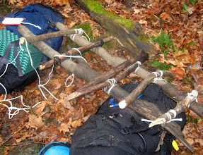 Photo: After an initial presentation by Dave, the teams traded off roles with ropework versus constructing an emergency litter (shown here still in progress).