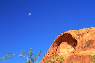 Photo: Une lune toujours présente au dessus des falaises rouges de Arches, près de Moab.
