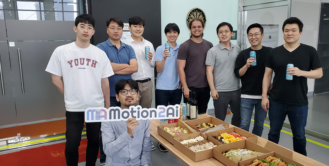 "The employees and founders of the Motion2ai startup are holding up a ""Motion2ai"" sign at a party."