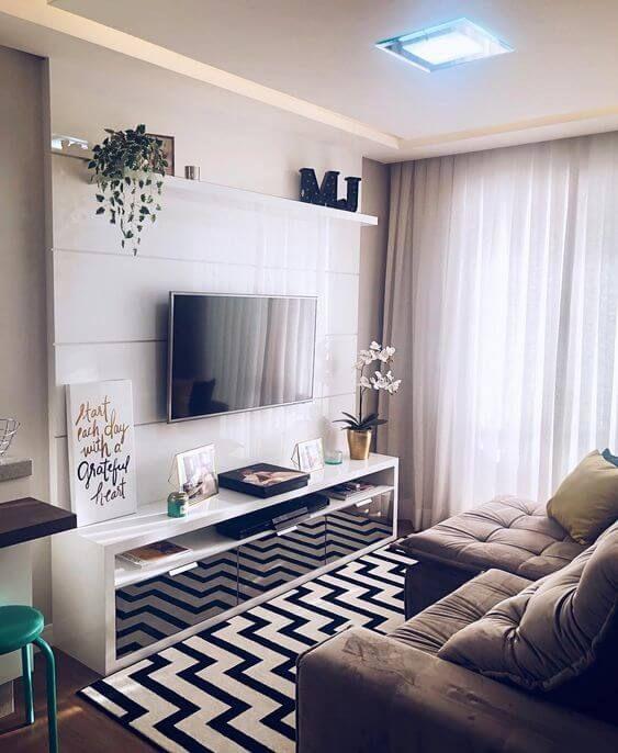 Rack branca com TV e objetos de decoração, sofá marrom, tapete com zig zag preto e branco e cortinas longa.