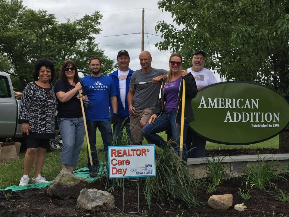 group of people with shovels standing next to Realtor Care Day sign
