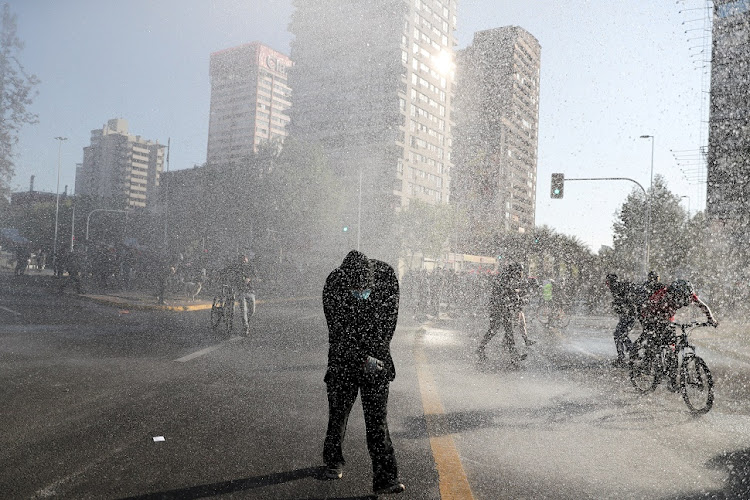 Antigovernment protesters are sprayed by a water cannon in Santiago, Chile.
