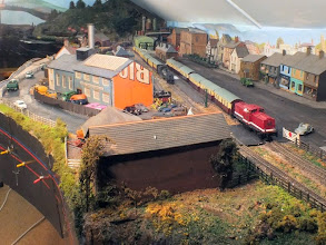 Photo: 005 Moving on to the right of the previous photo we pass the main station area, which with a layout that is 30ft x 14ft is clearly going to still be a work in progress for some time to come. The main components are however fully in place, just a bit of rendering to the orange washing powder carton at the end of the factory building required !