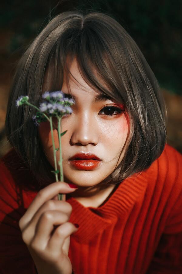 Foto de uma mulher asiática posando com uma flor na mão