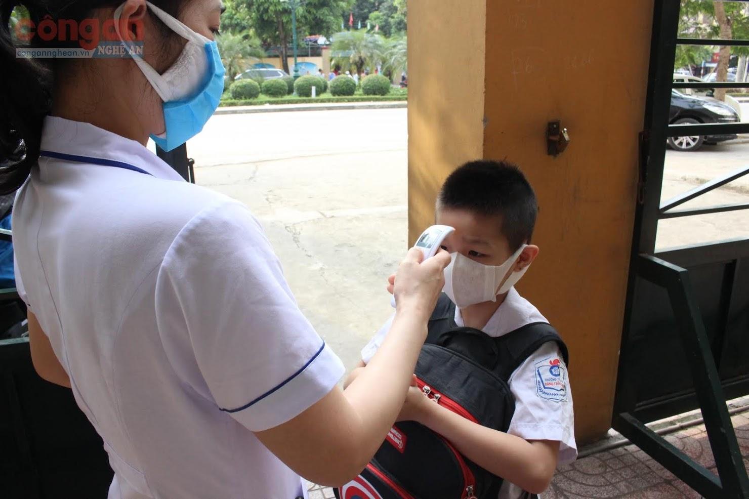 Các em học sinh trường Tiểu học Hồng Sơn được đo nhiệt độ trước lúc vào cổng