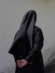 Zuster in zwart met sluier, op de rug gezien